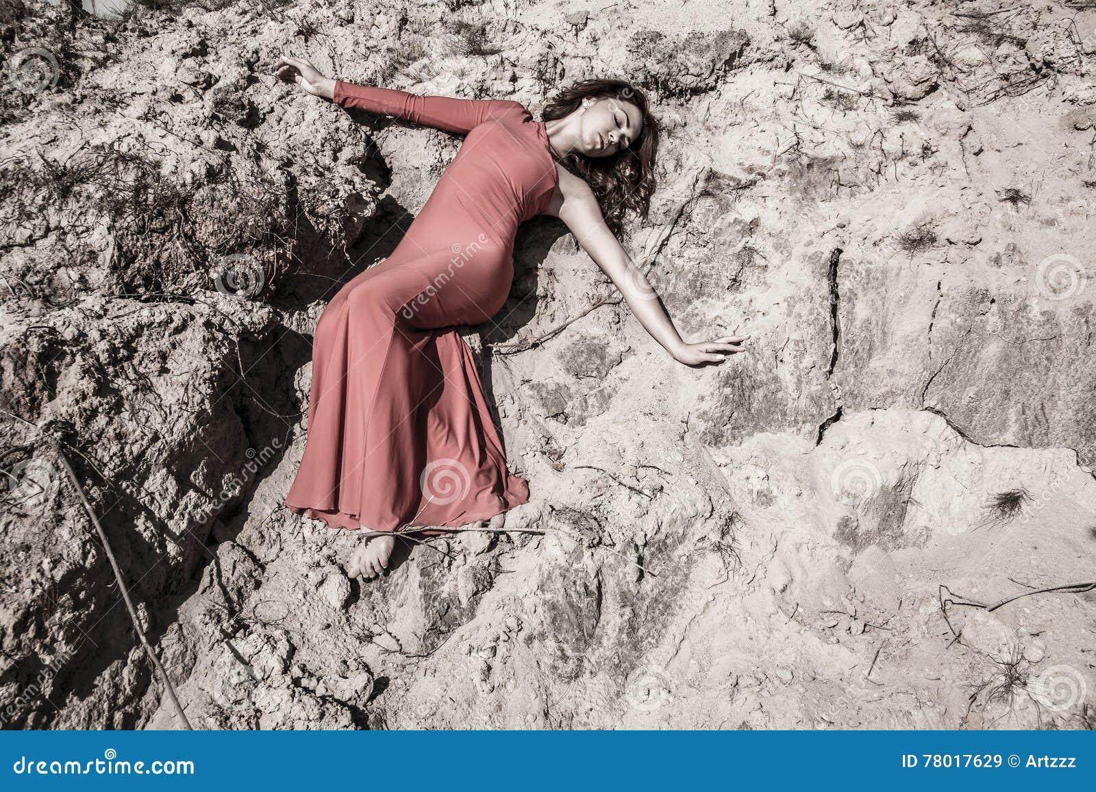 Dame die in kleding in het vuil leggen