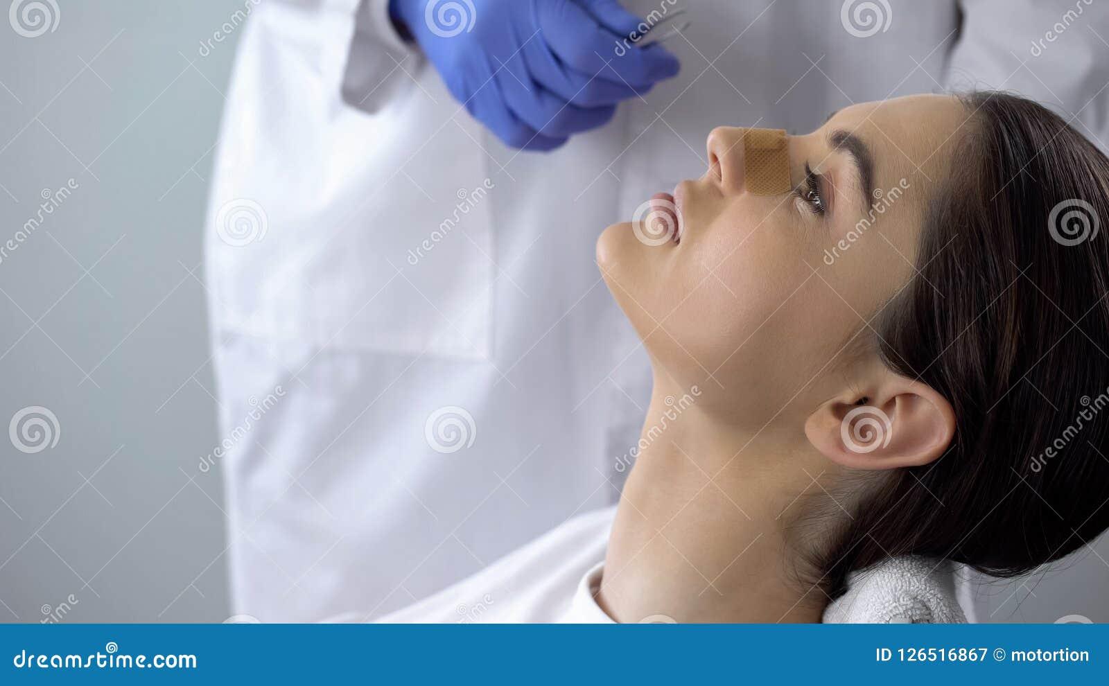 Dame met pleister op neus, arts die patiëntengezicht na plastische chirurgie onderzoeken