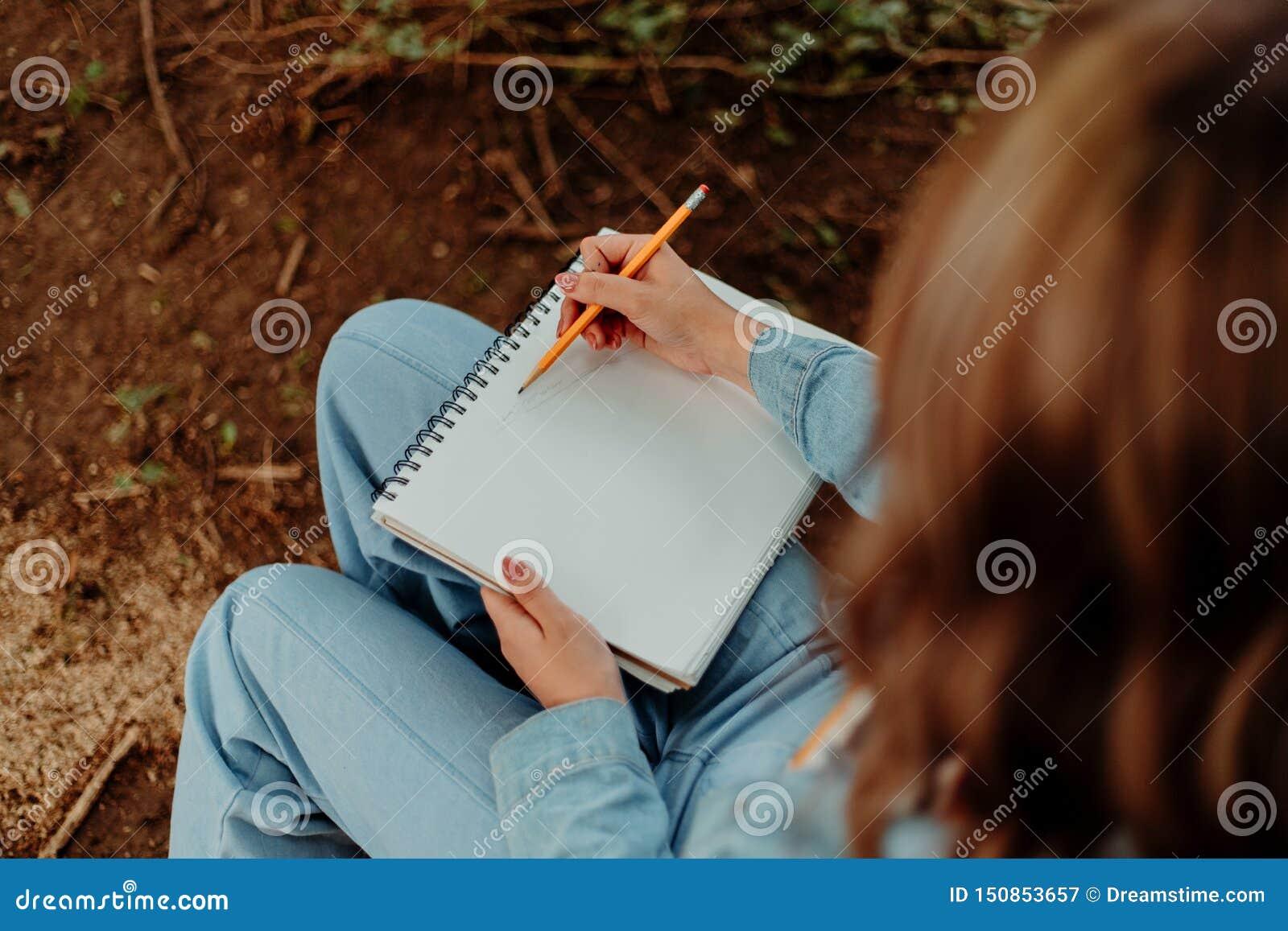 Dame Sketching Outside im Notizbuch