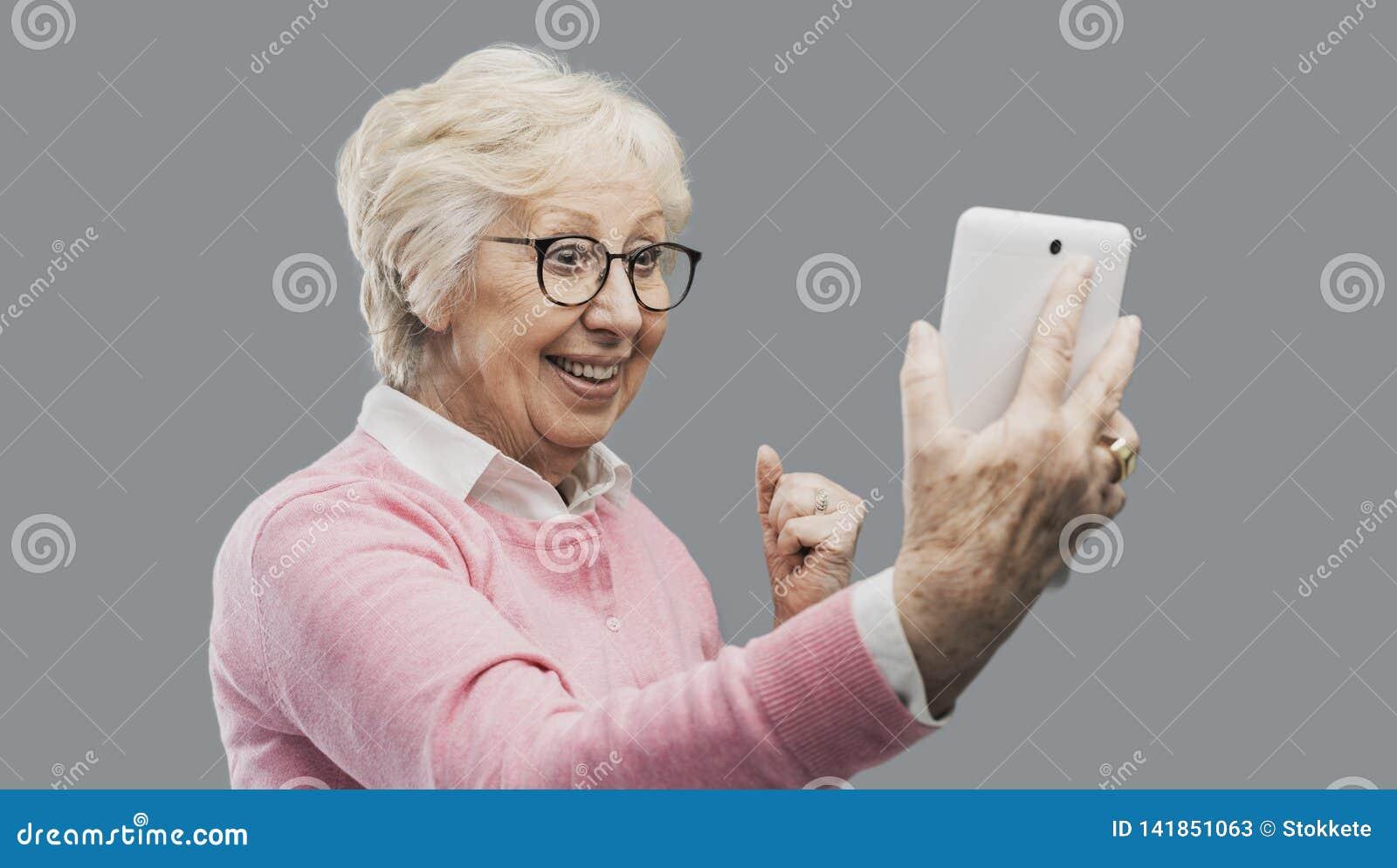 Dame supérieure étonnée heureuse utilisant un comprimé numérique