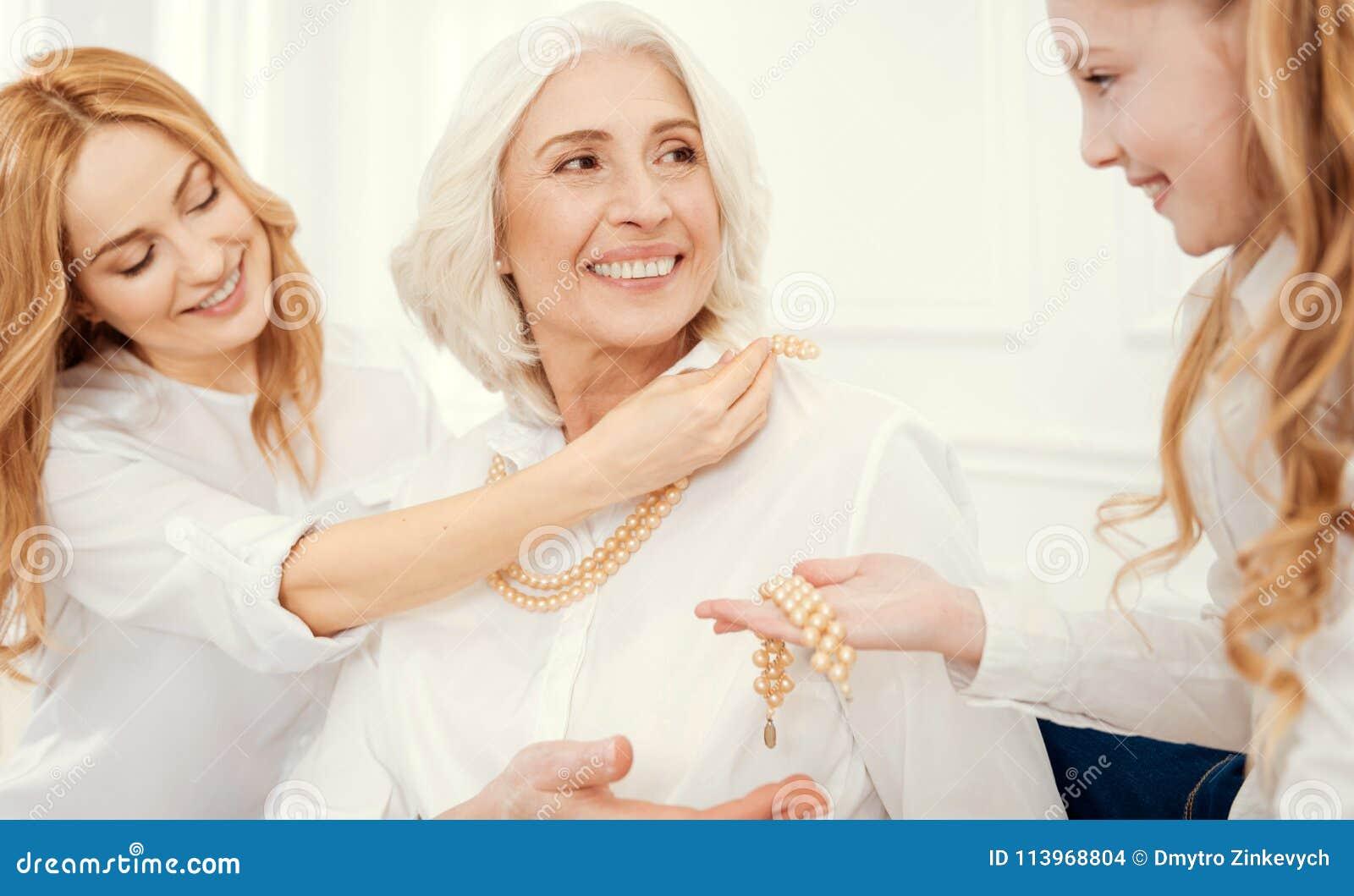 Dame supérieure joyeuse passant le temps girly avec la fille et l petit-enfant