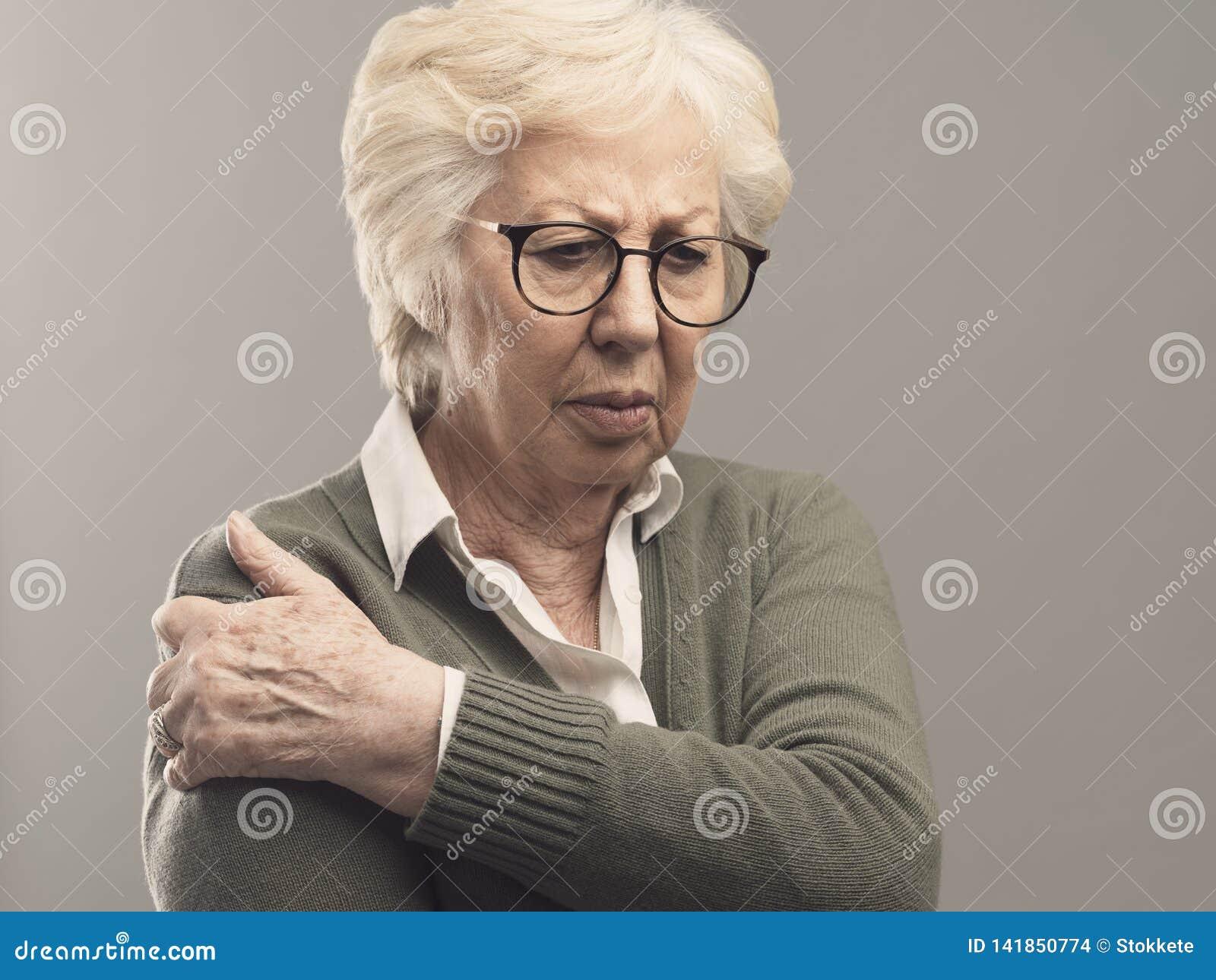 Dame supérieure triste avec le bras et douleurs articulaires