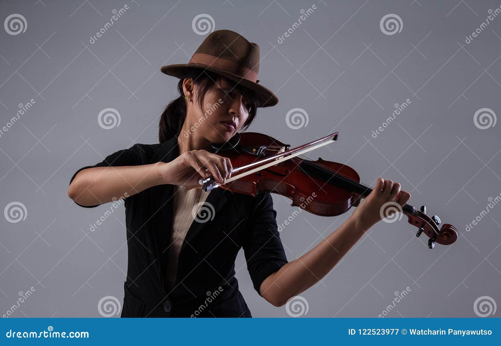 Damen med den bruna hatten spelar fiolen, satte fiolen på vänster skuldra och rymmer pilbågefiolen med assistenten