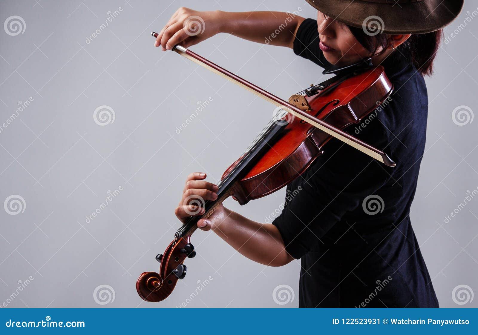Damen med den svarta dräkten och hatten för kläder som bruna spelar fiolen