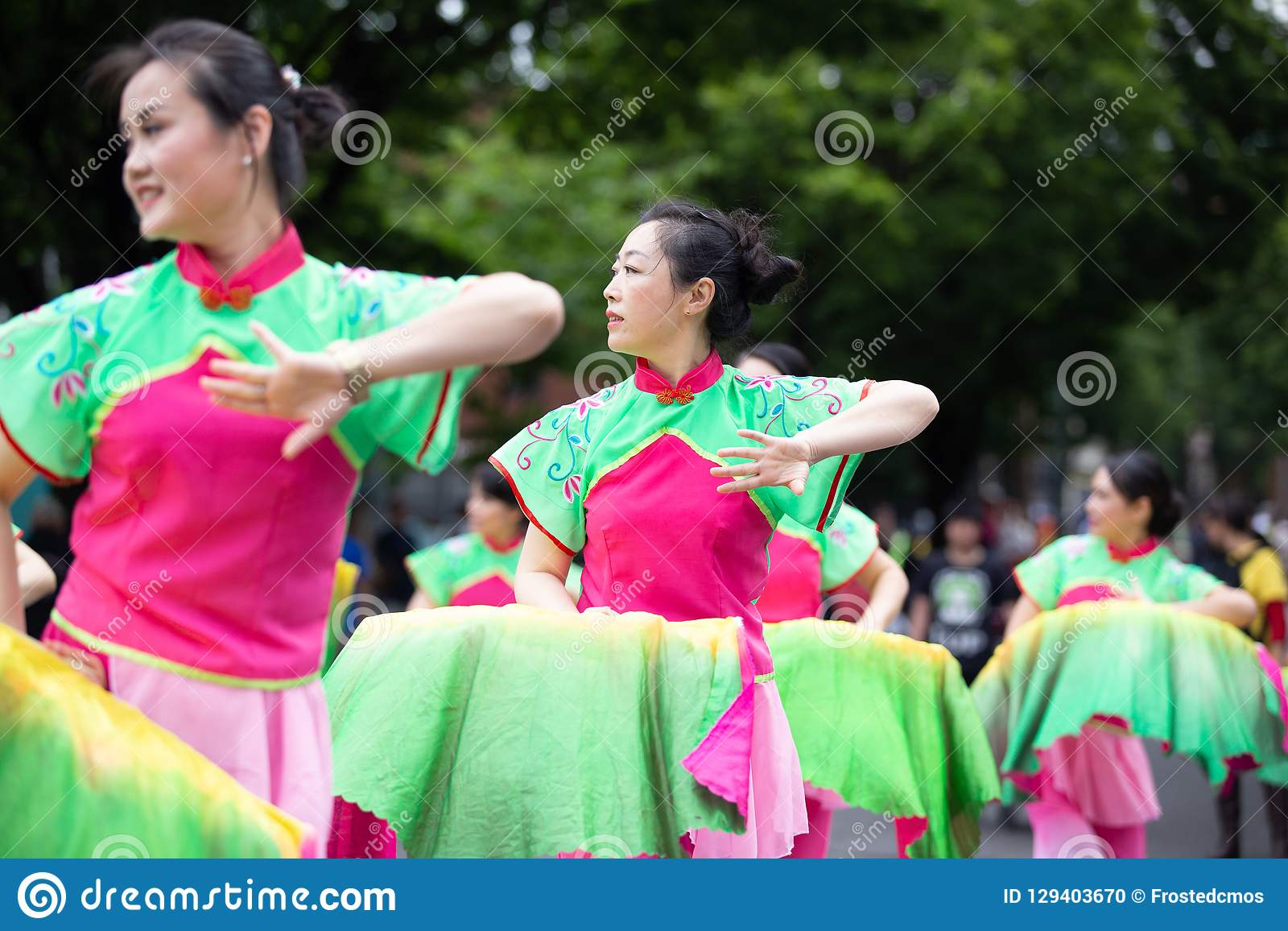 Dames asiatiques dans la danse traditionnelle de costume sur la rue
