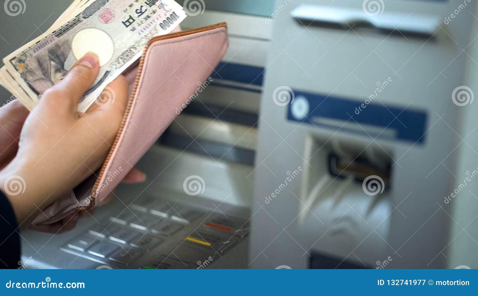 Dameshanden die Japanse die Yen in portefeuille, contant geld zetten van ATM, het reizen wordt teruggetrokken