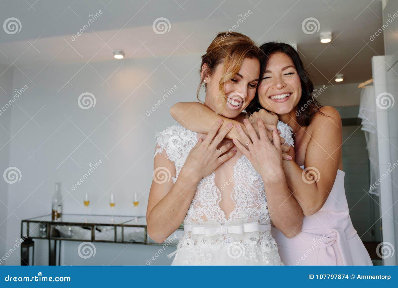Damigella d onore felice che dà un abbraccio tenero alla sposa