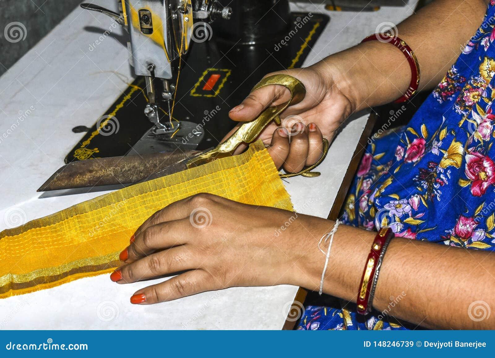 Damskräddaren av Indien som klipper kläder med, scissor och gör klänningen vid symaskinen