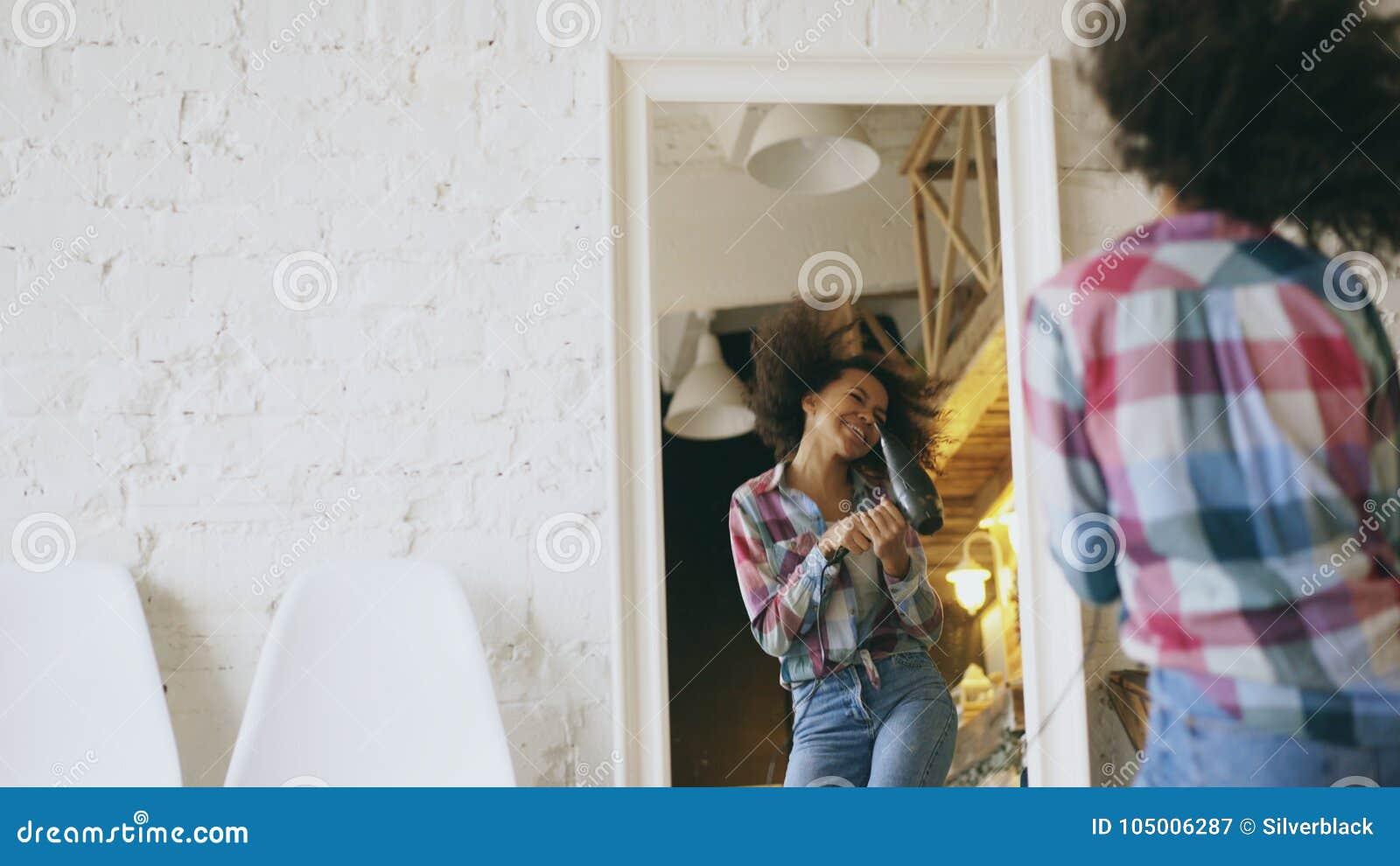 Dança afro-americano engraçada encaracolado da menina e canto com o secador de cabelo na frente do espelho em casa