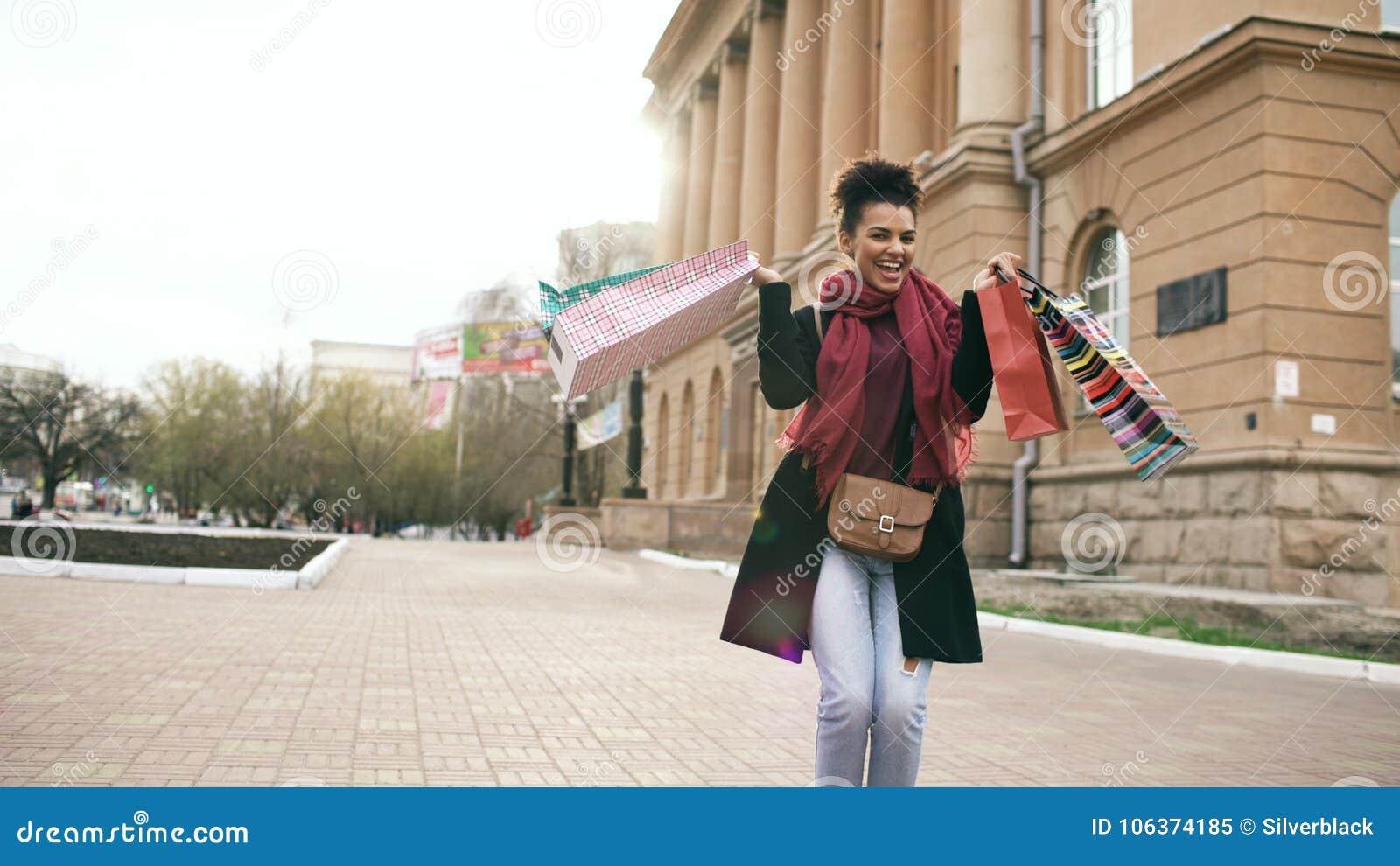 A dança atrativa da menina da raça misturada e tem o divertimento ao andar abaixo da rua com sacos Jovem mulher feliz que anda em