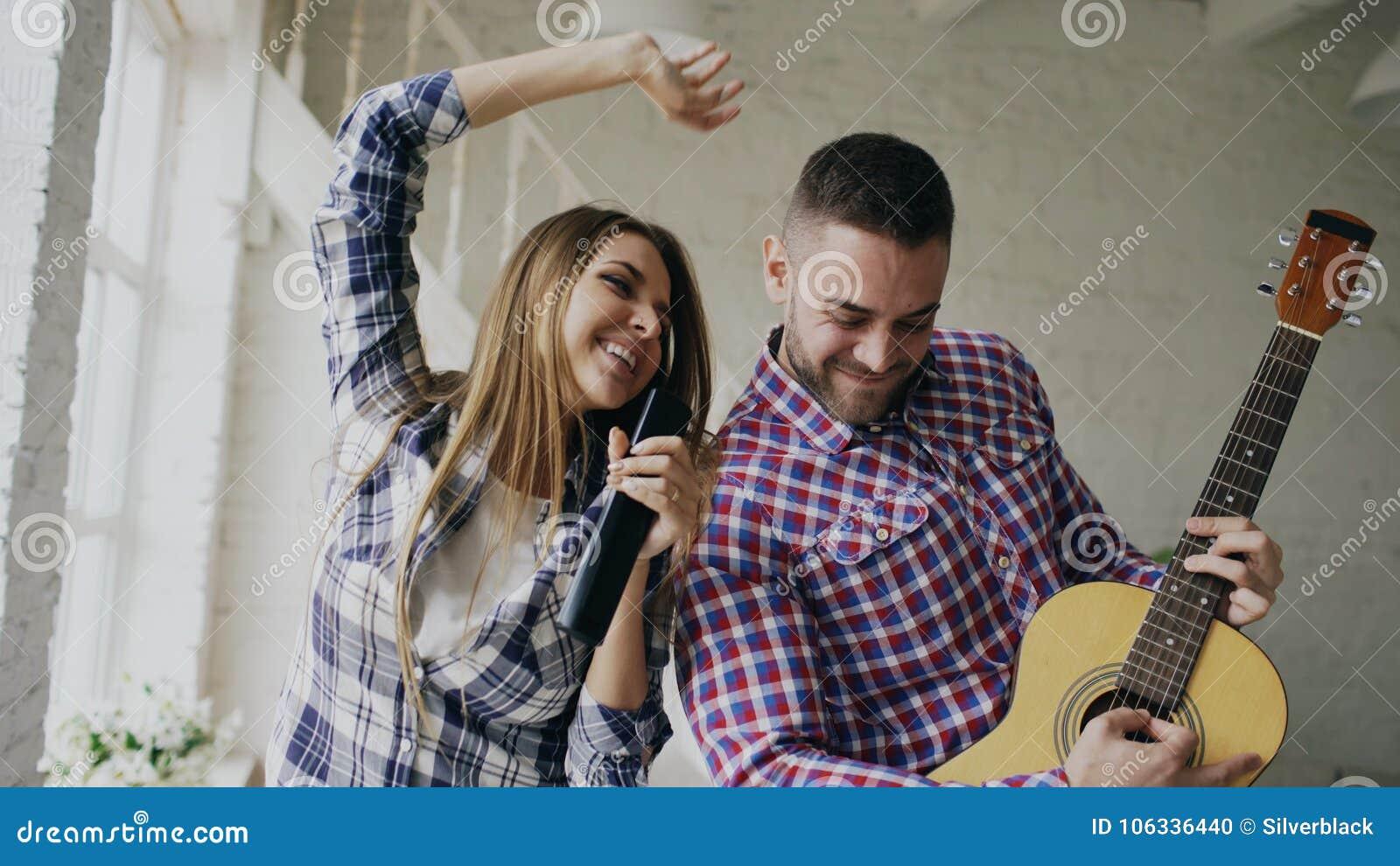 Dança feliz e loving engraçada dos pares e guitarra do jogo O homem e a mulher têm o divertimento durante seu feriado em casa