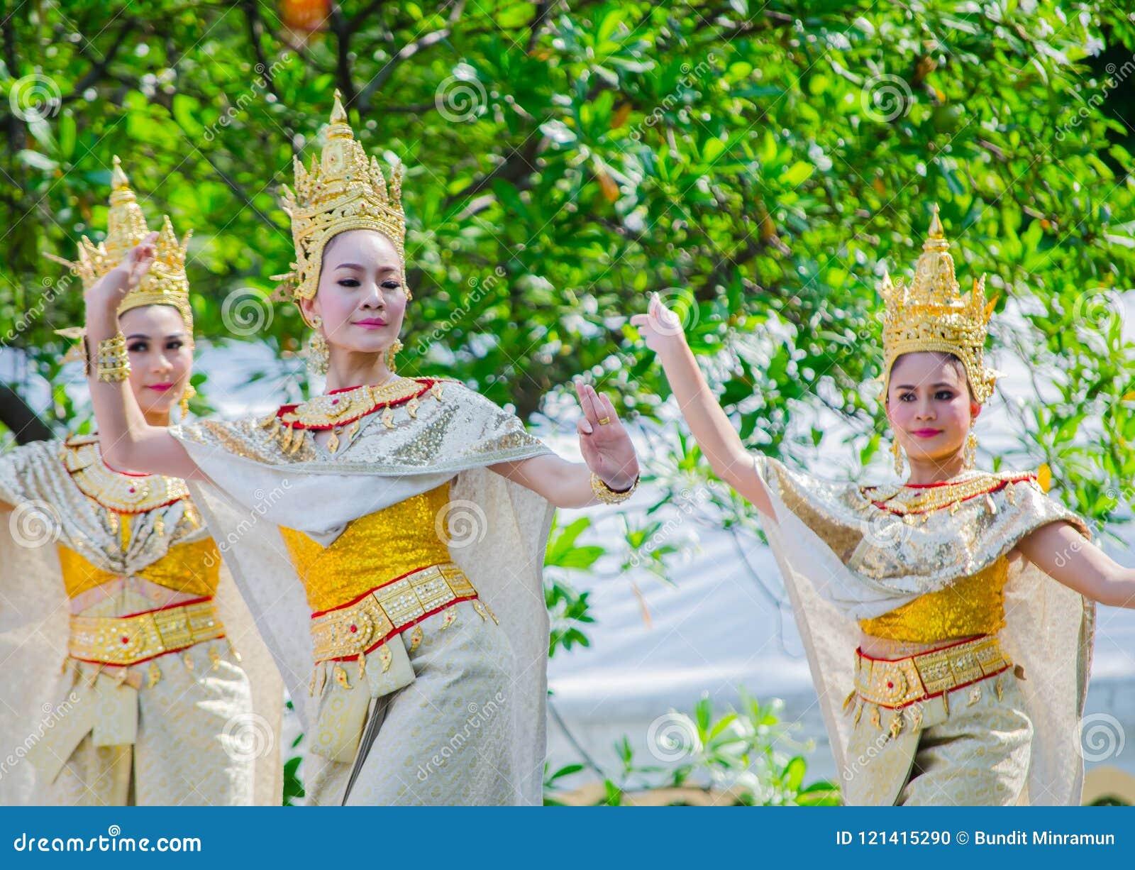 Dança tradicional tailandesa com a mulher bonita no traje cultural dourado que executa na fase para o festival de Songkran