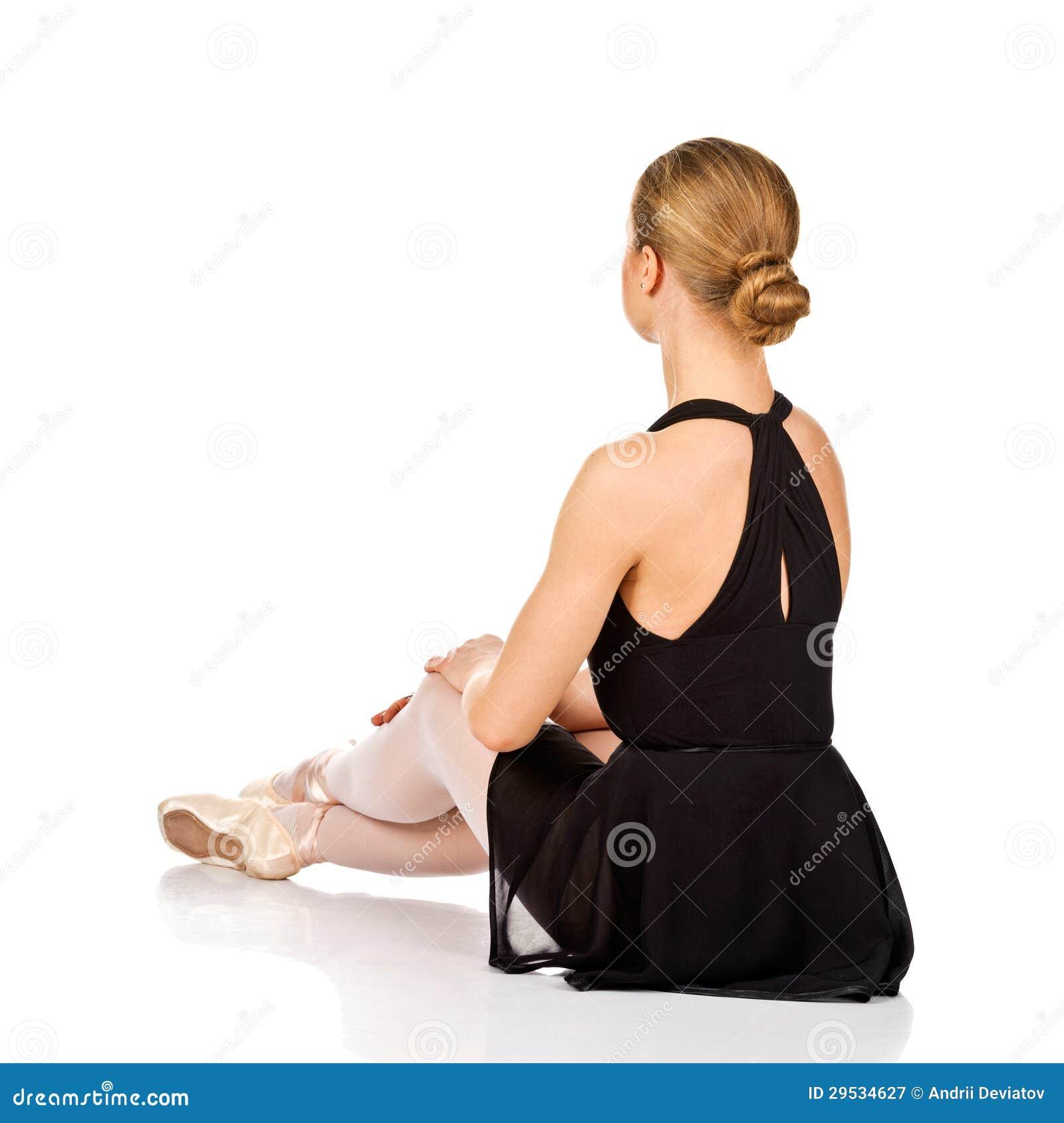 Dançarino de bailado elegante que senta-se no assoalho. Vista traseira