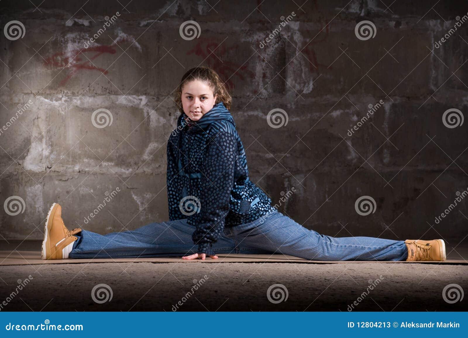 Dançarino do lúpulo do quadril no estilo moderno sobre a parede de tijolo