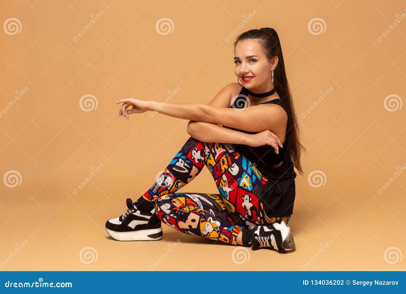 Dançarino fêmea novo no fundo do estúdio Menina moderna nova do dançarino do estilo que senta-se no assoalho no estúdio