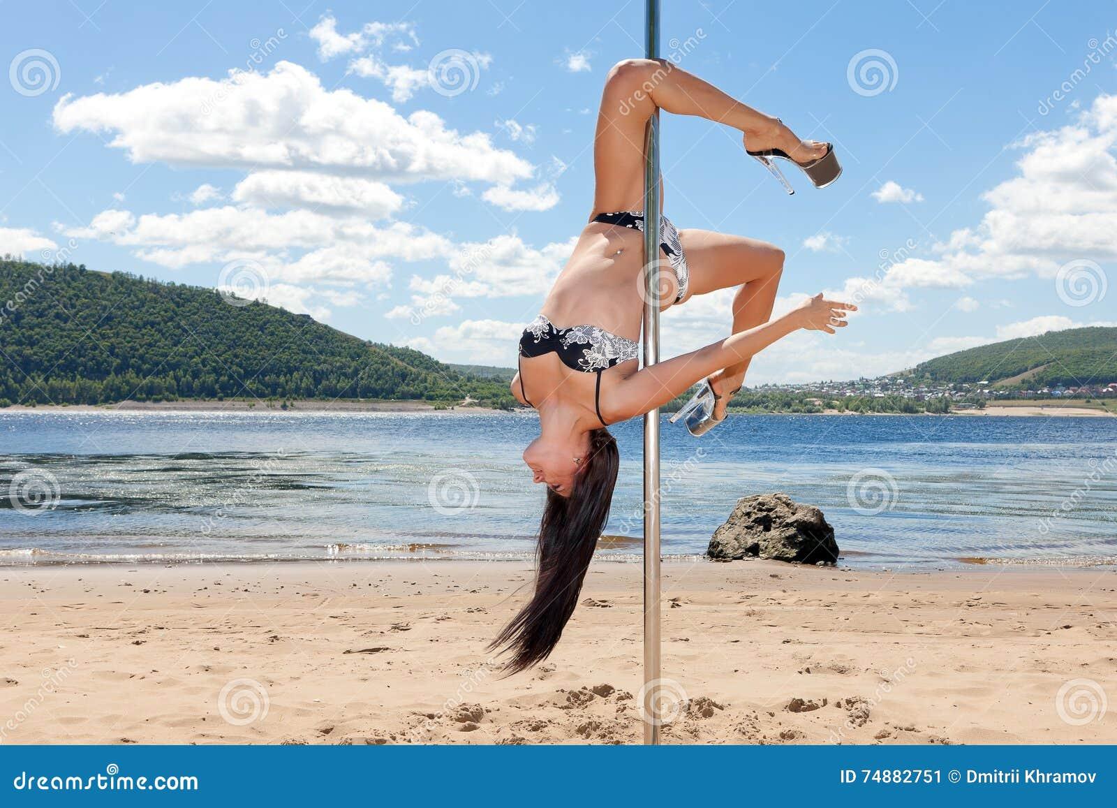 Dançarino no fundo de cabeça para baixo do polo da praia do verão e do céu azul
