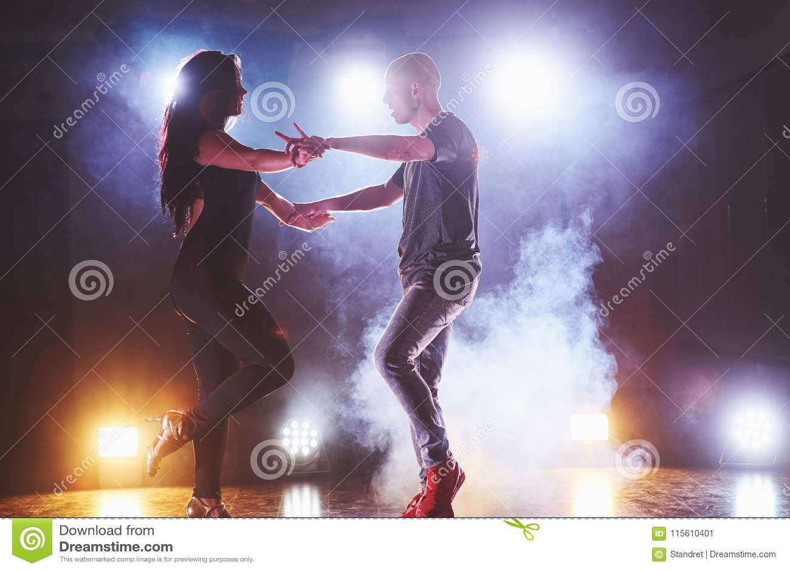 Dançarinos hábeis que executam na sala escura sob a luz e o fumo do concerto Pares sensuais que executam um artístico