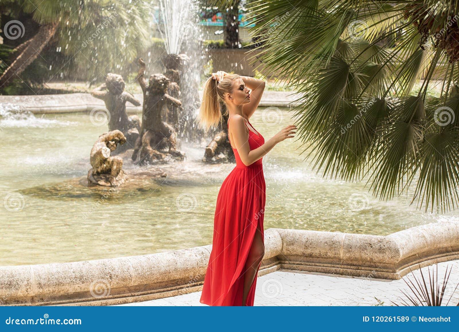 Dana den blonda kvinnan i den röda maxi klänningen som poserar i trädgård