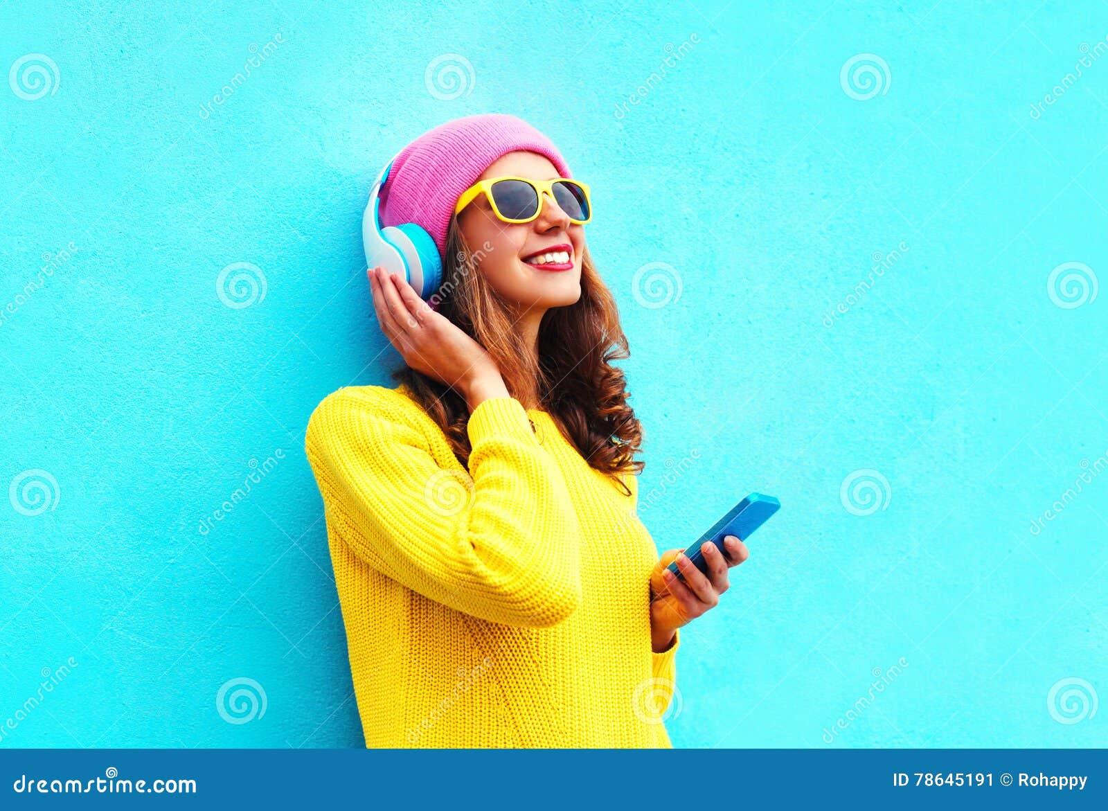 Dana den nätta söta bekymmerslösa flickan som lyssnar till musik i hörlurar med smartphonen bärande färgrik rosa solglasögon för