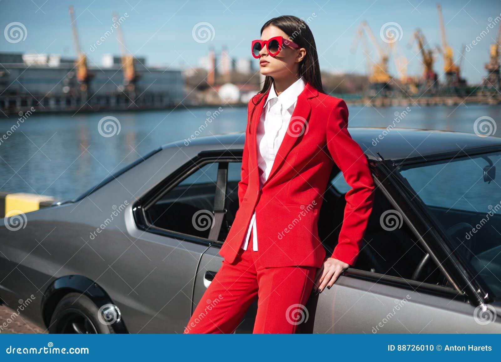 Dana flickaanseendet bredvid en retro sportbil på solen Stilfull kvinna i en röd dräkt och solglasögon som väntar nära den klassi