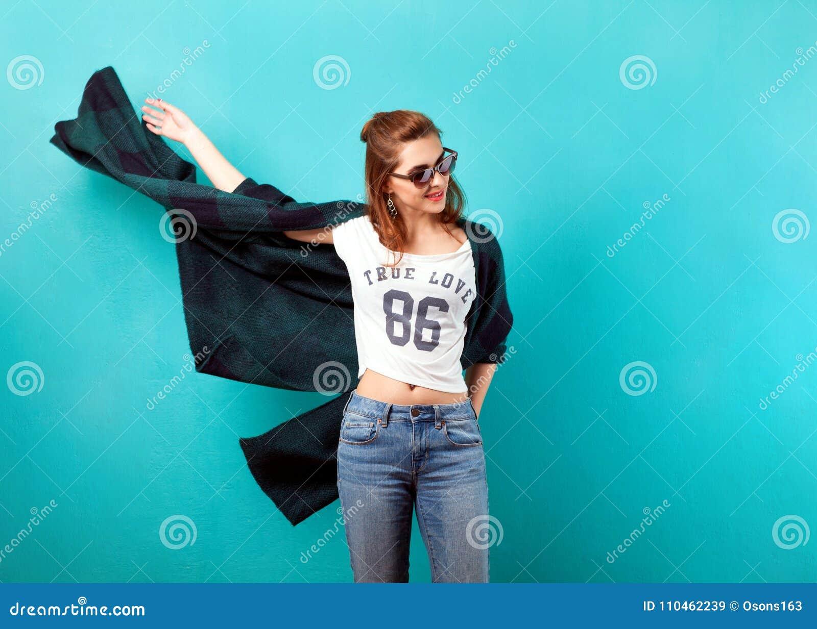 Dana flickan i studio nära turkosbakgrund som ler sinnesrörelse
