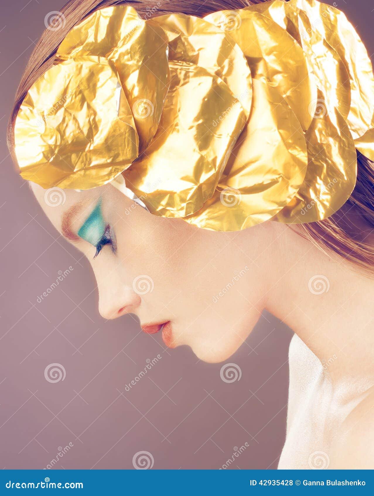 Dana flickan med guld- garnering på huvudet, blå makeup