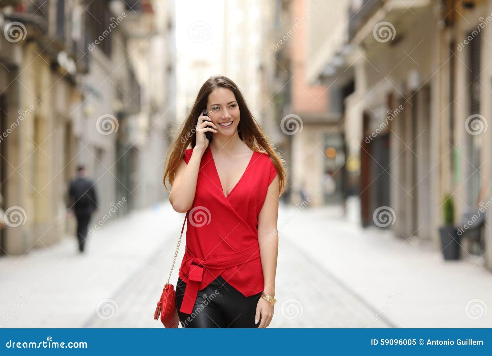 Dana kvinnan som går och talar på mobiltelefonen