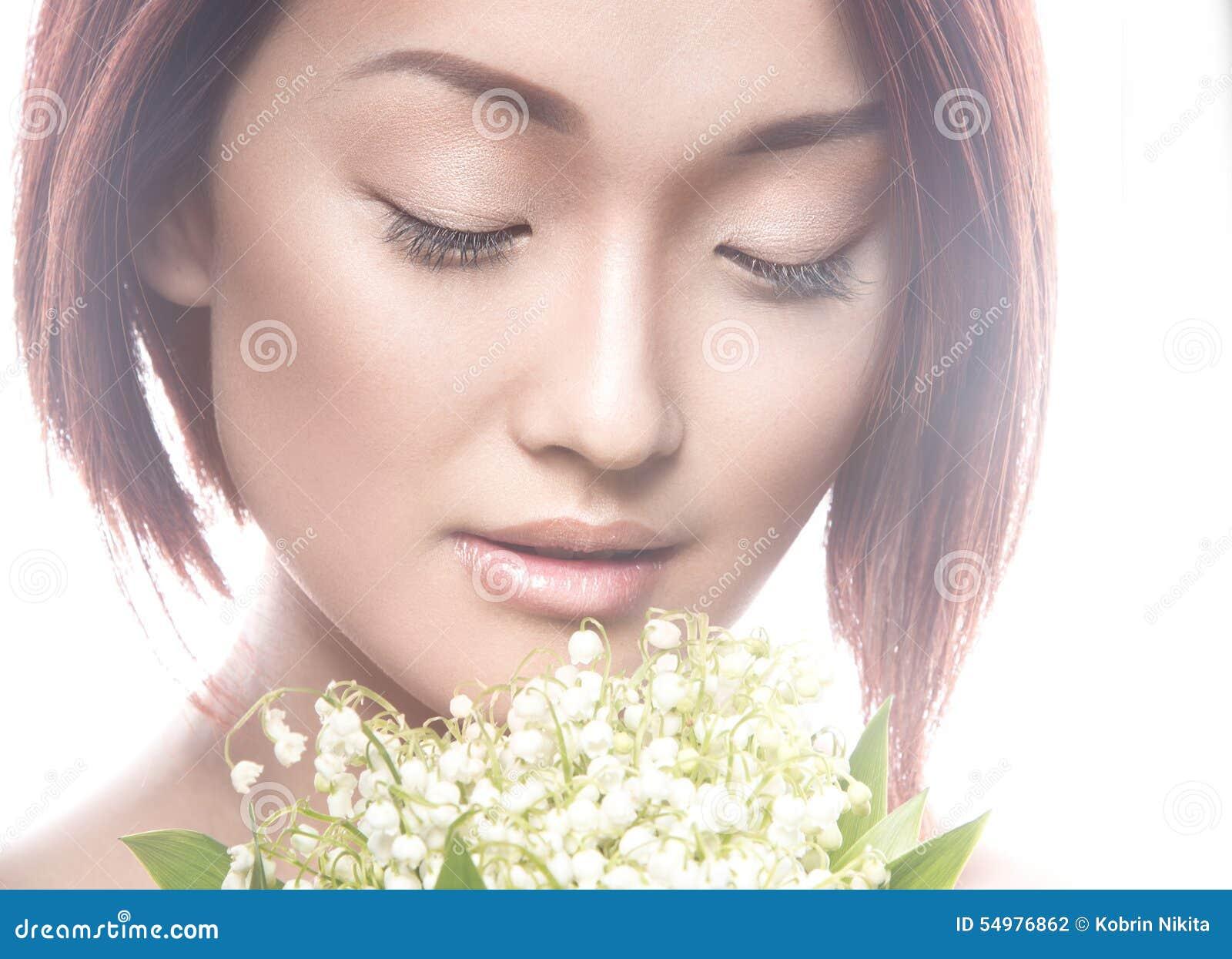 Dana orientalisk typ för den härliga flickan med delikat naturligt smink och blommor Härlig le flicka
