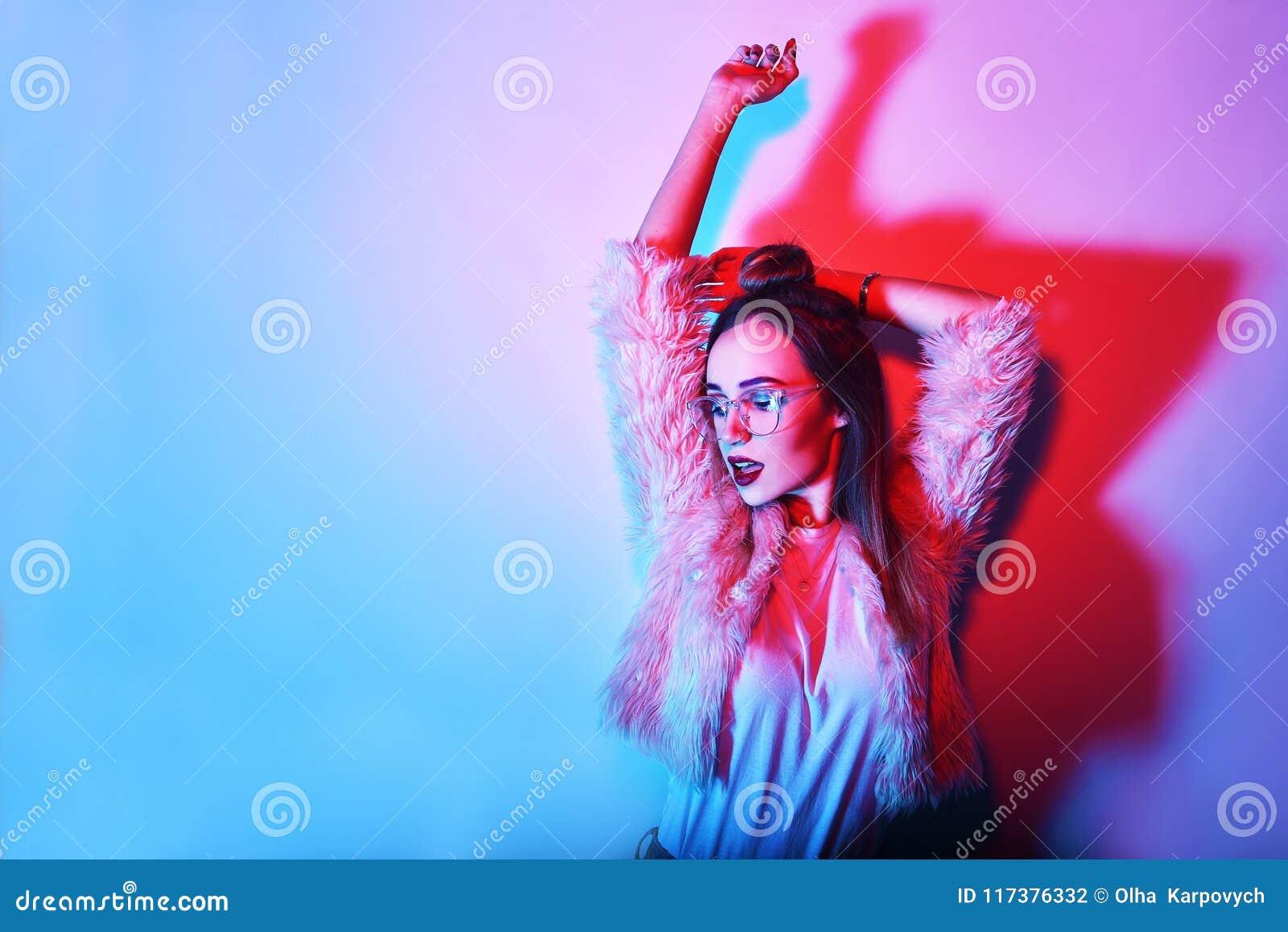 Dana ståenden av den unga eleganta flickan i exponeringsglas Kulör bakgrund, studioskott Härlig brunettkvinna hipsterflickadans