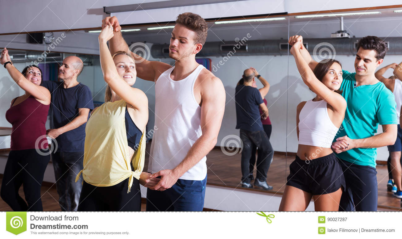 Dancing couples learning salsa