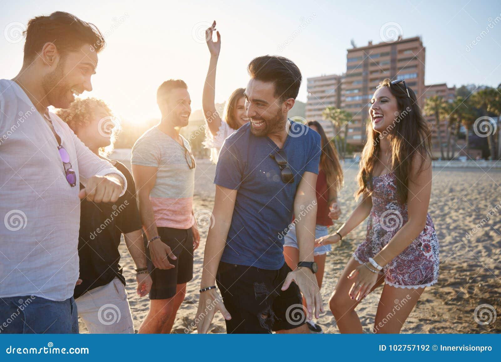 Dancing del giovane con gli amici sulla risata della spiaggia