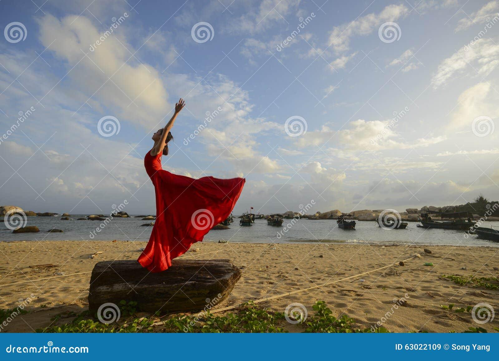 Dancing della donna accanto alla spiaggia