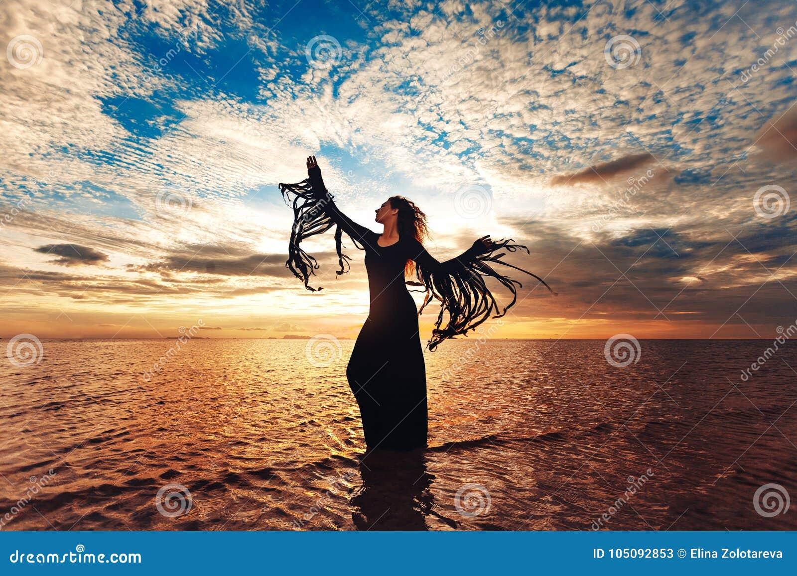 Dancing della donna elegante sull acqua Tramonto e siluetta