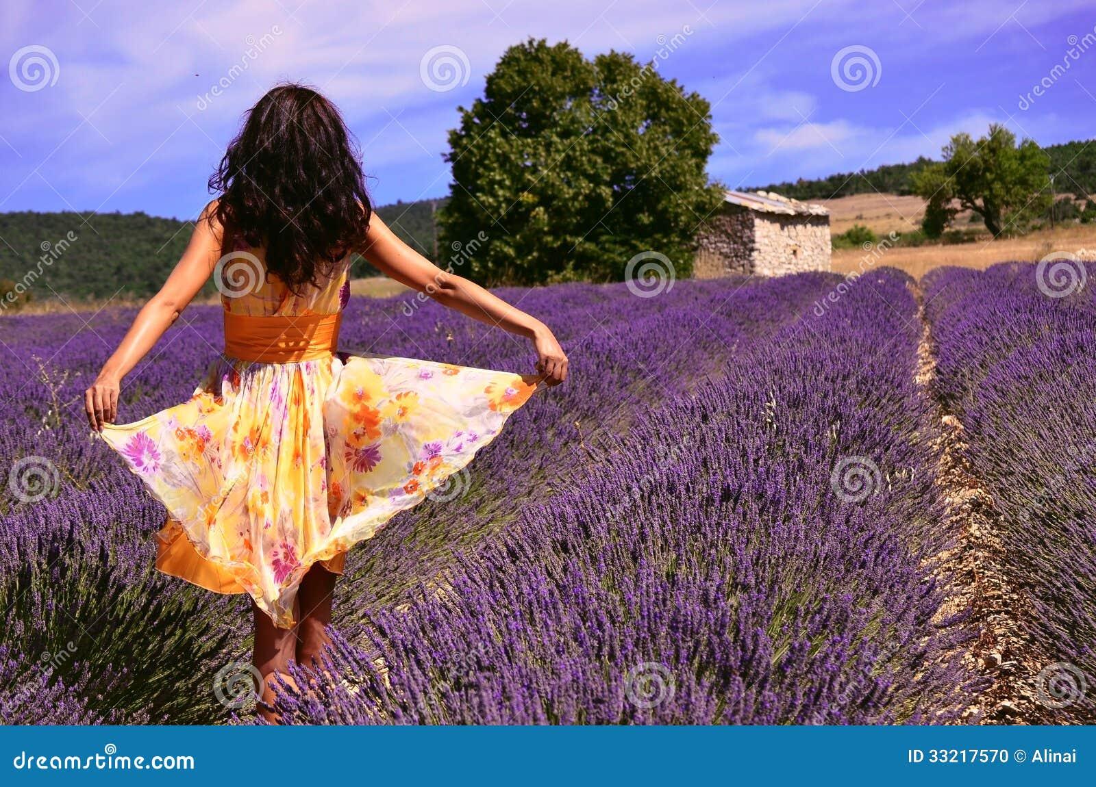 Woman wearing a floating dress in a lavender field