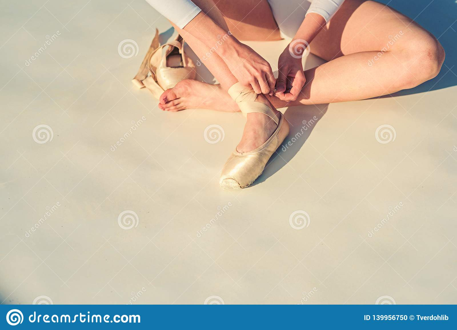 Dancing on pointe. Ballerina shoes. Ballerina legs in white ballet shoes. Lacing ballet slippers. Female feet in pointe