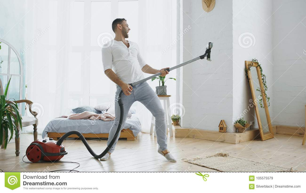 Young man having fun cleaning house with vacuum cleaner dancing like guitarist