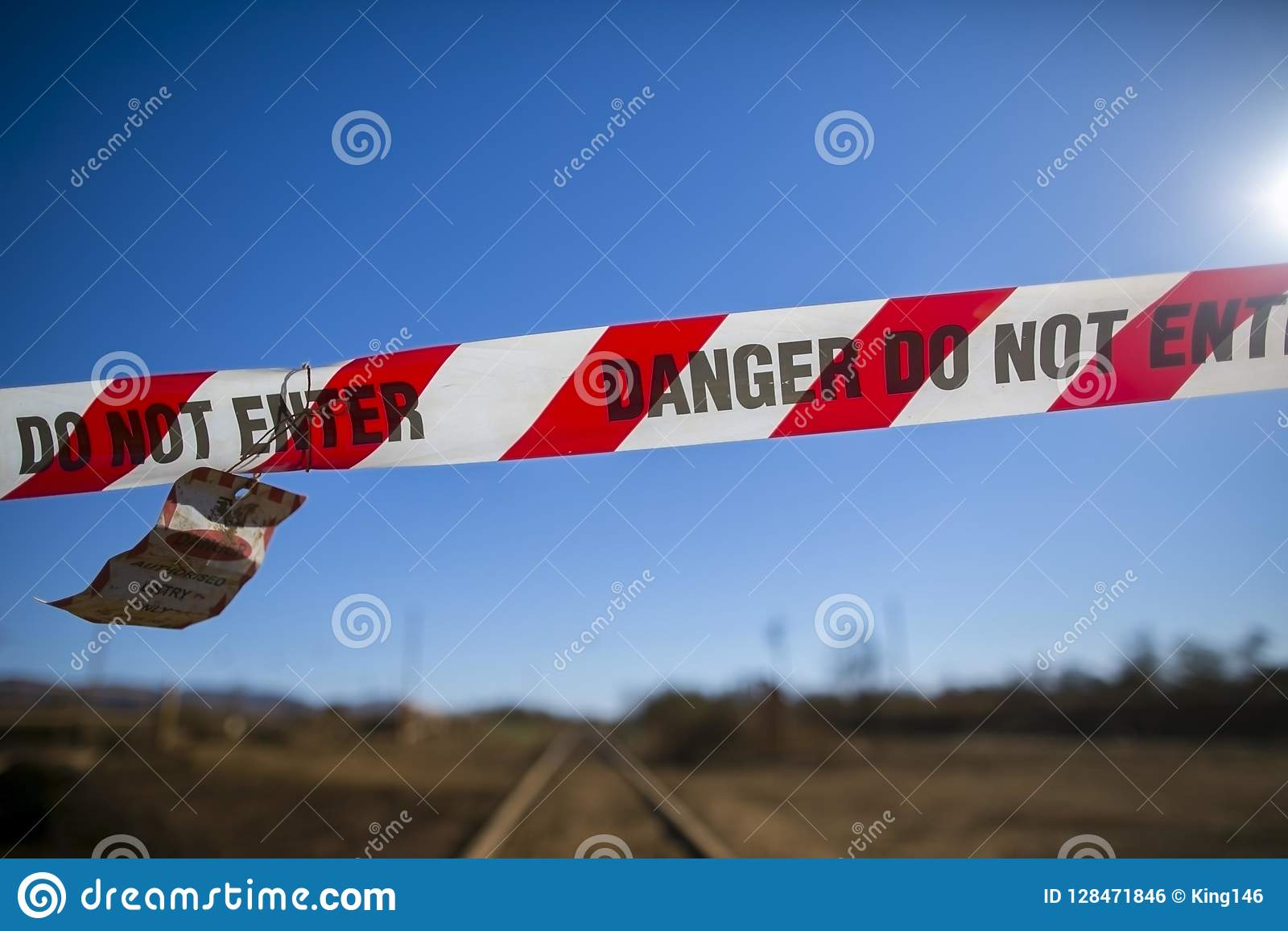 Danger red and white tape barricade exclusion zone area with written authorised personnel entry only on train track