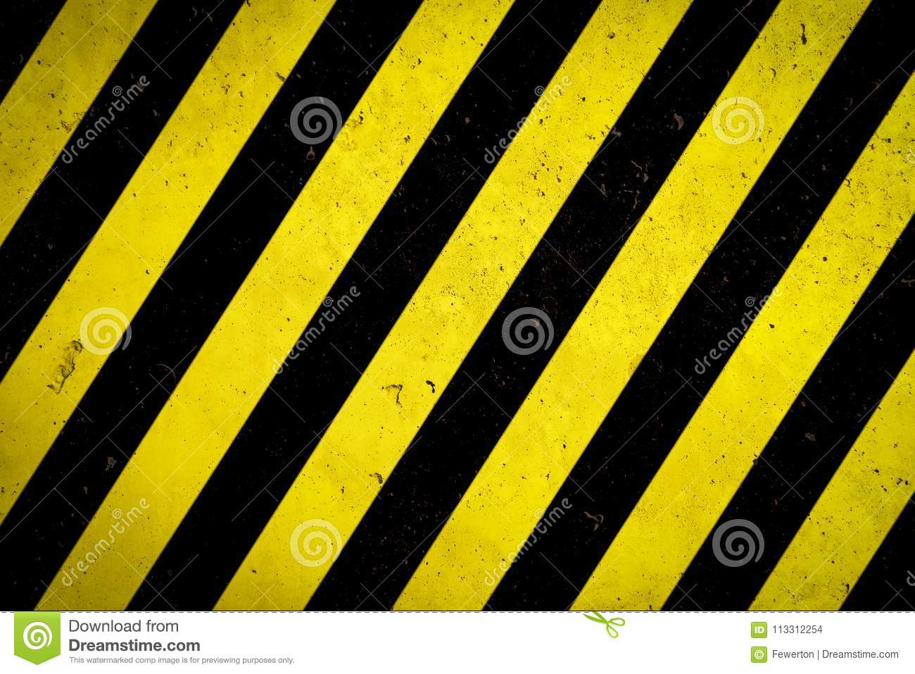 Danger zone: Warning sign yellow and black stripes painted over concrete wall coarse facade with holes and imperfections texture