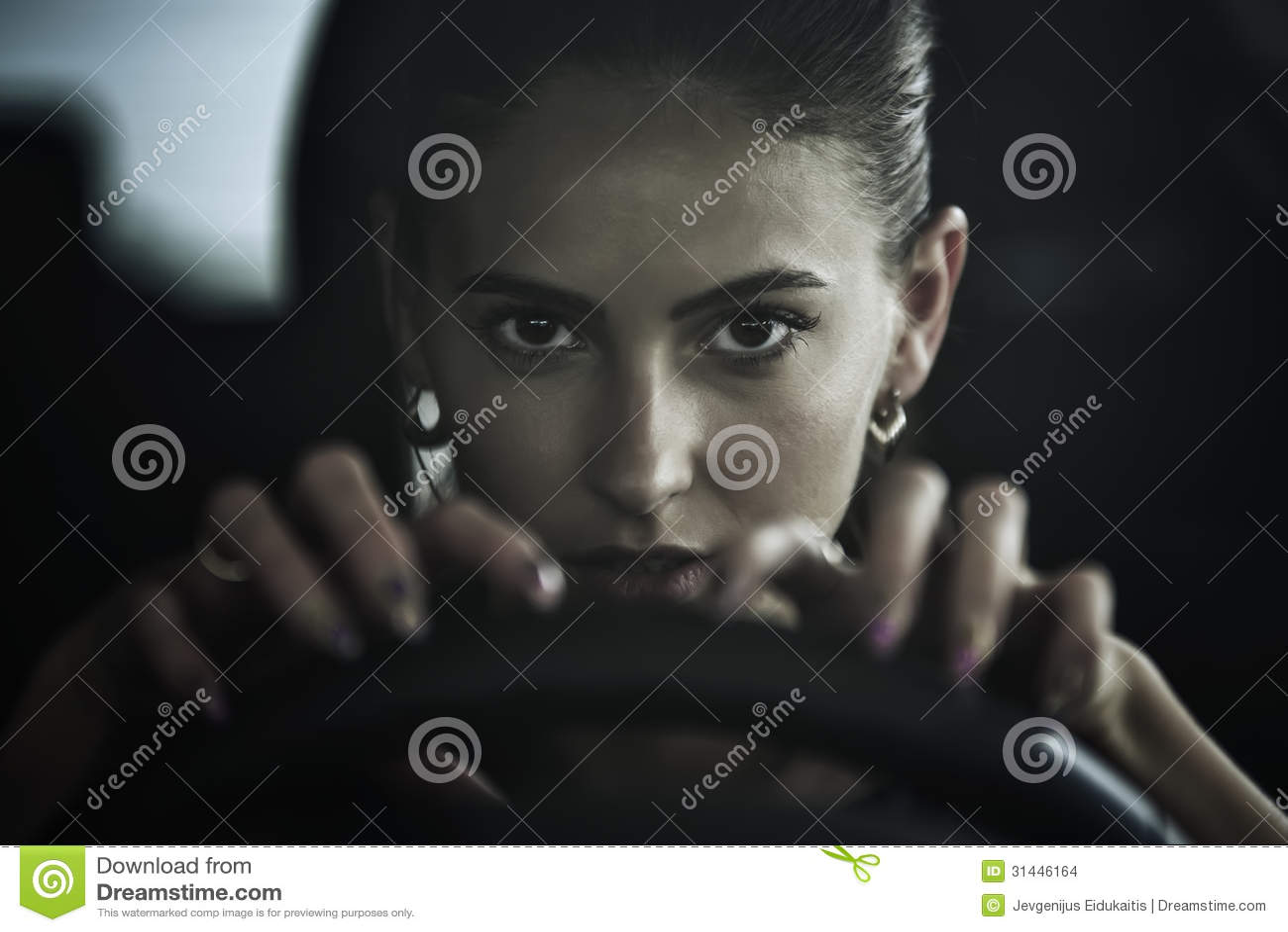Dangerous beauty woman driving a car, close up portrait