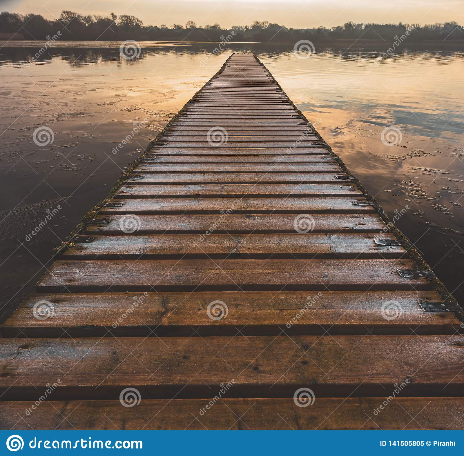 A dangerous frozen wooden walkway leads out into the middle of a lake