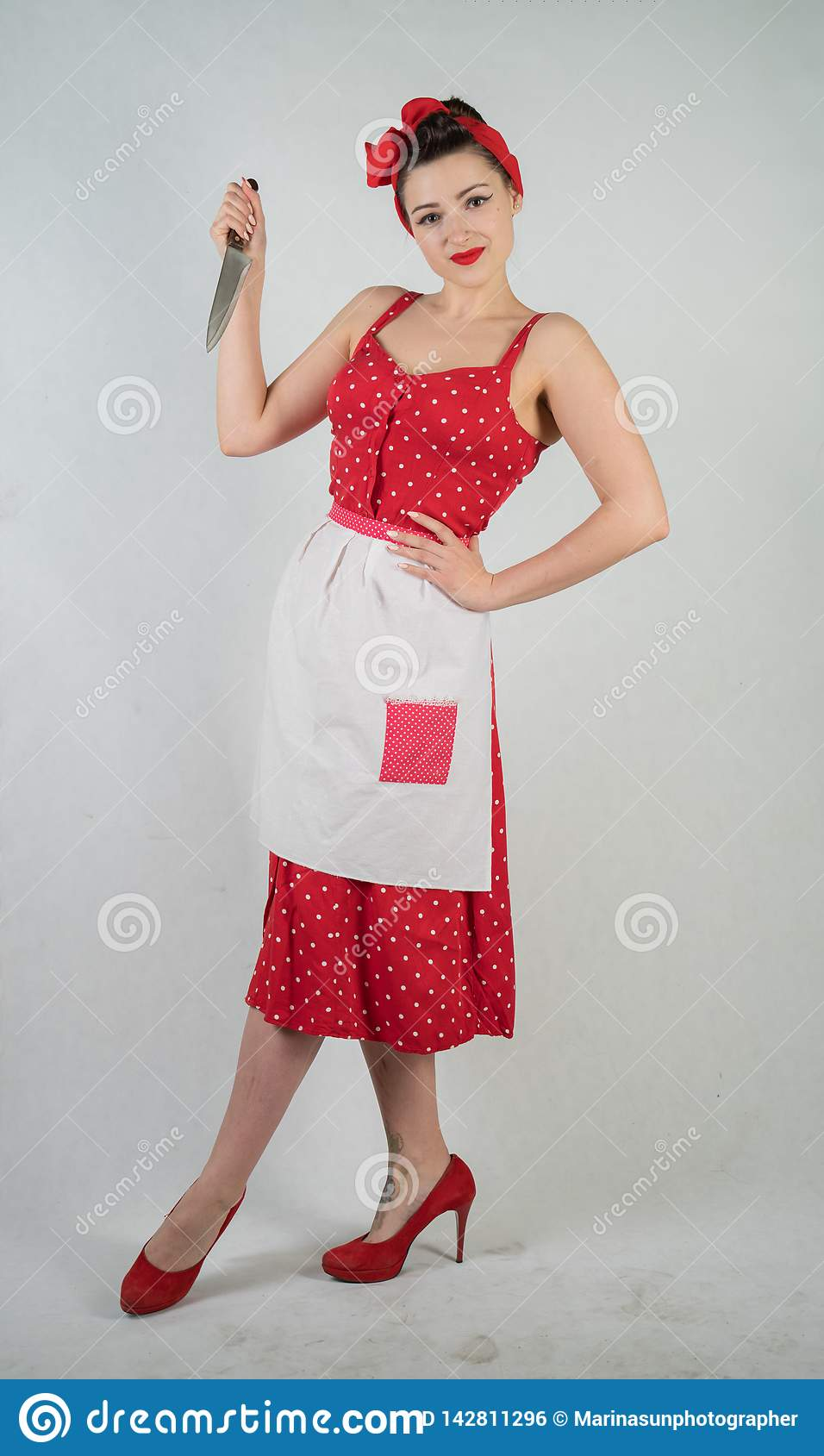 Dangerous pin up girl housewife in red vintage polka dot dress stands with a huge kitchen knife in her hands and angrily rejoices