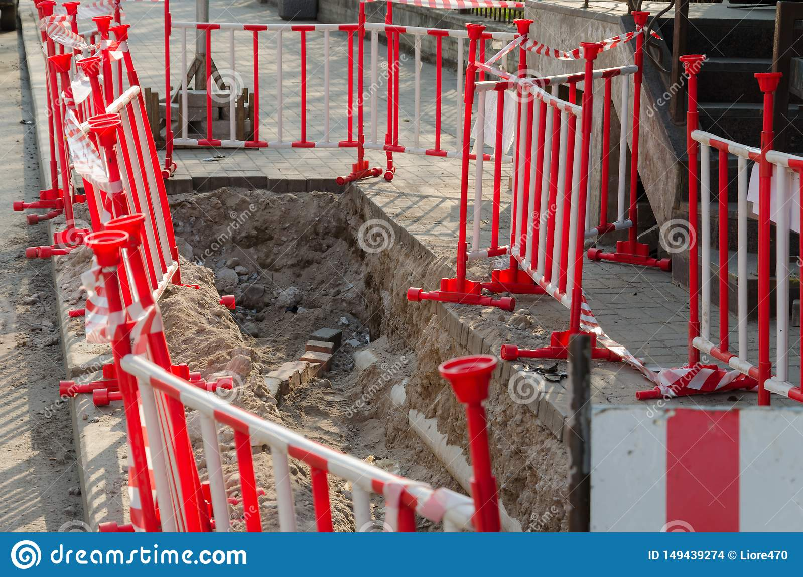 Dangerous pit on the sidewalk surrounded by warning red-and-white barriers. Repair of paving slabs