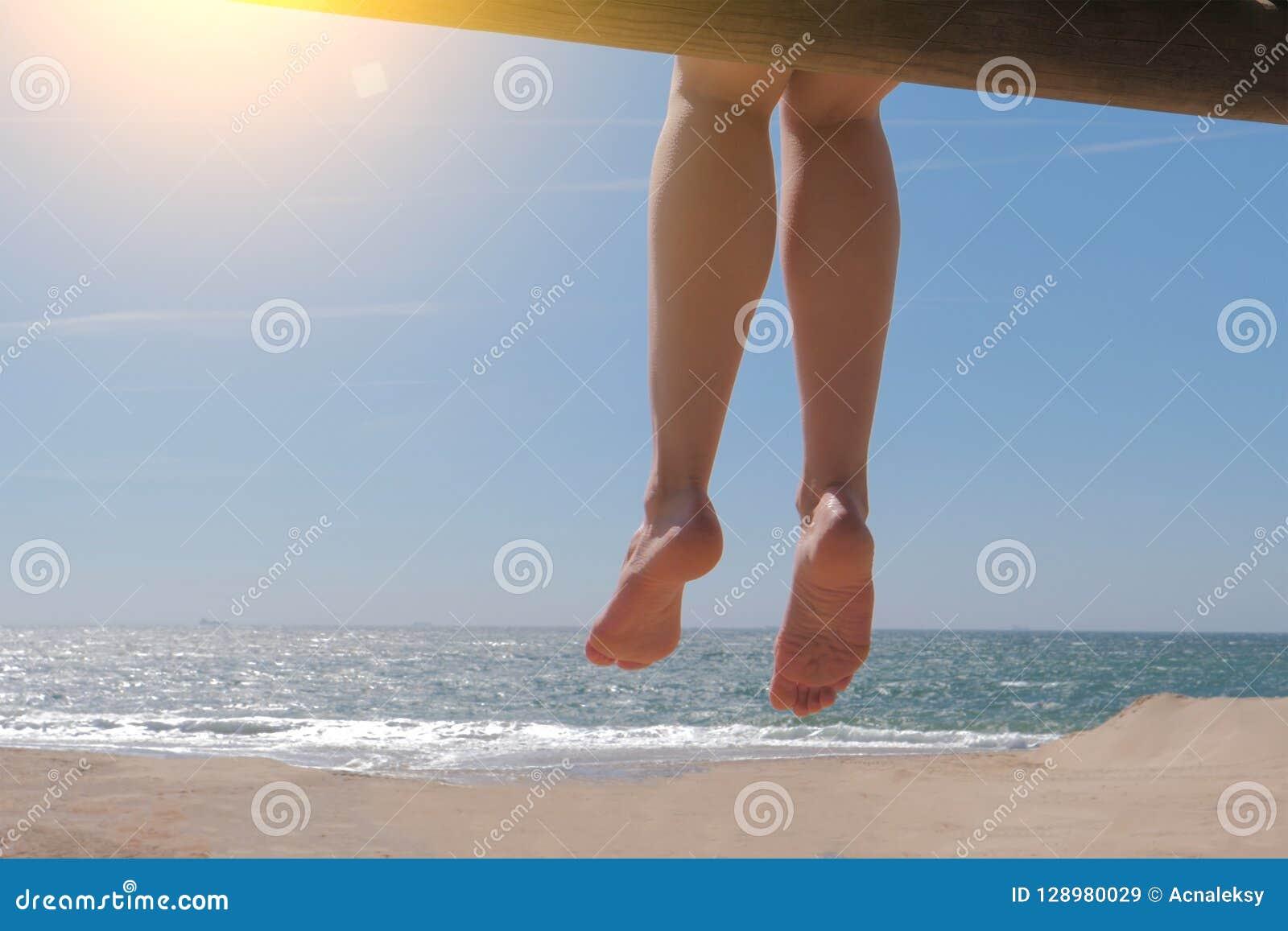 Dangling bare female feet sitting on beach.