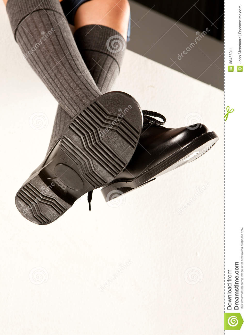99eed18df1 A dangling set of kids legs with long grey socks and black school shoes on  a white background