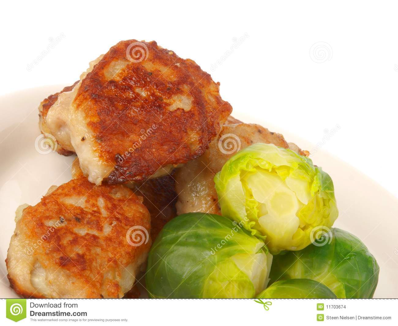 Danish meatballs with Brussels sprouts. Close up on white background.
