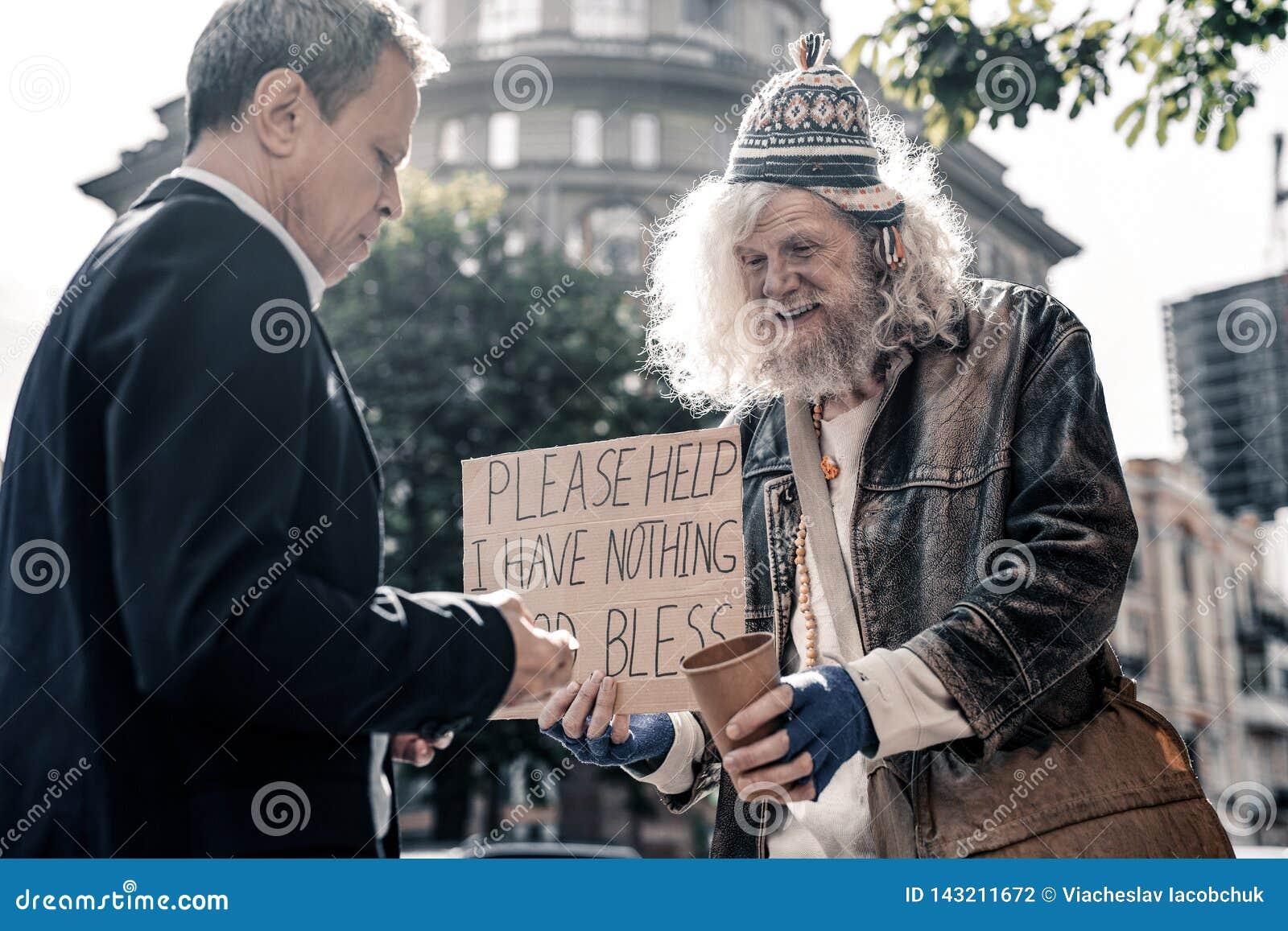 Dankbarer langhaariger alter Mann, der leere Kaffeetasse vorschlägt