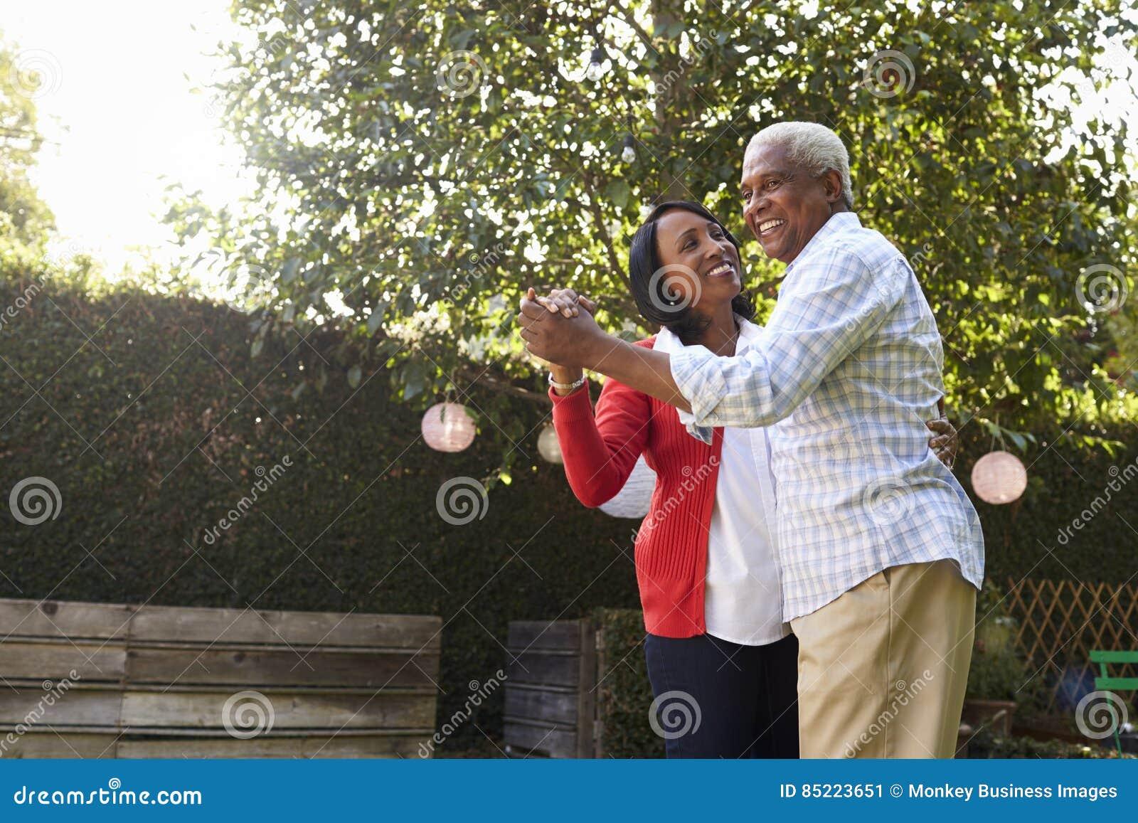 Dans för pensionärsvartpar i deras tillbaka trädgård