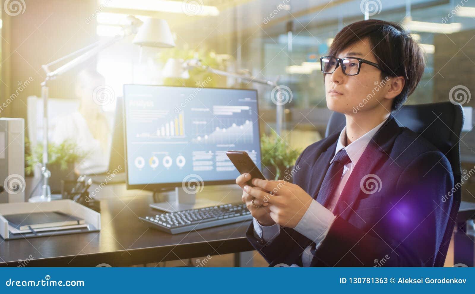 Dans l homme d affaires asiatique est Uses Smartphone de bureau, lutin de dactylographie