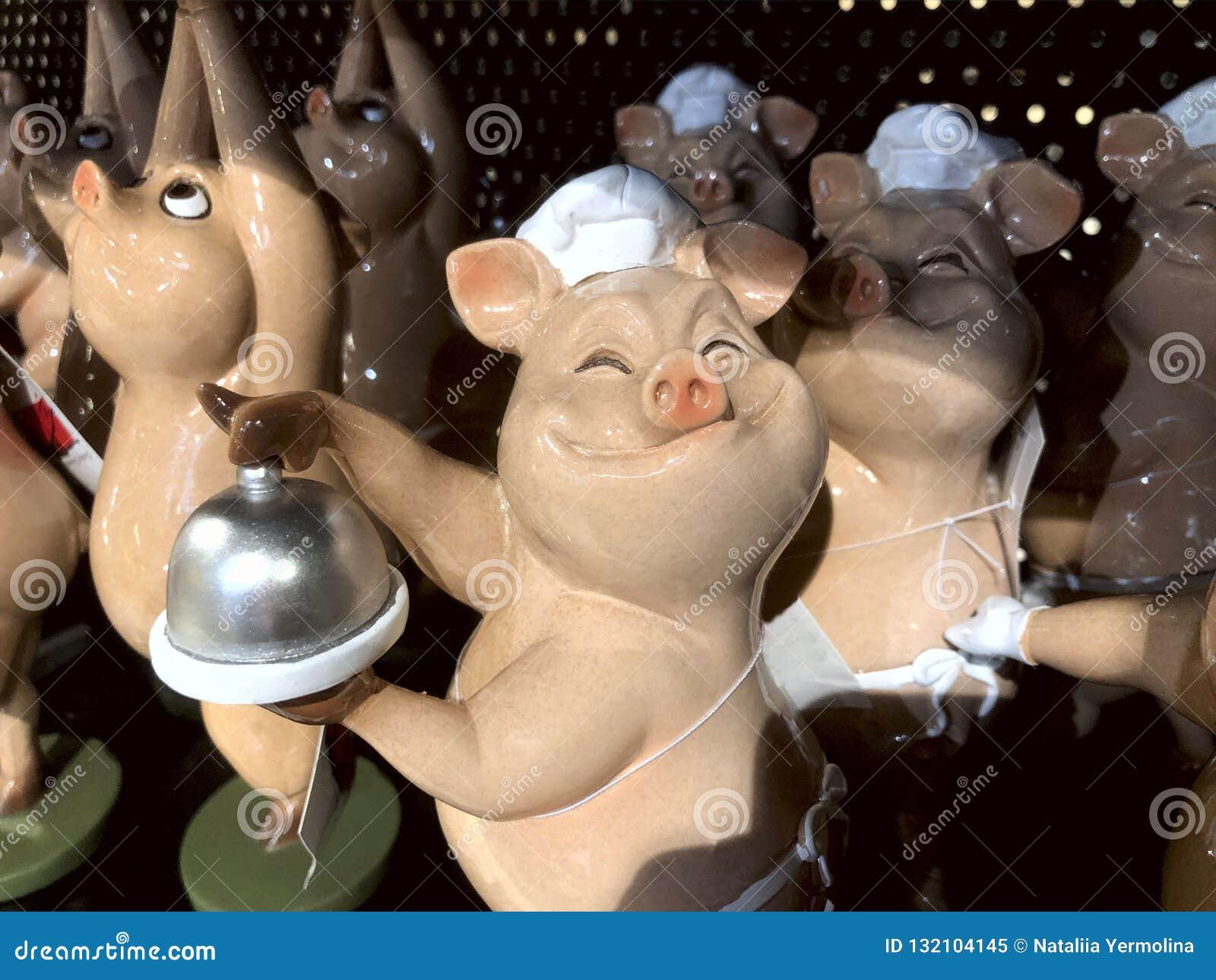 Dans la fenêtre de magasin chez les porcs colorés de jouets de magasin dans des chapeaux de chef