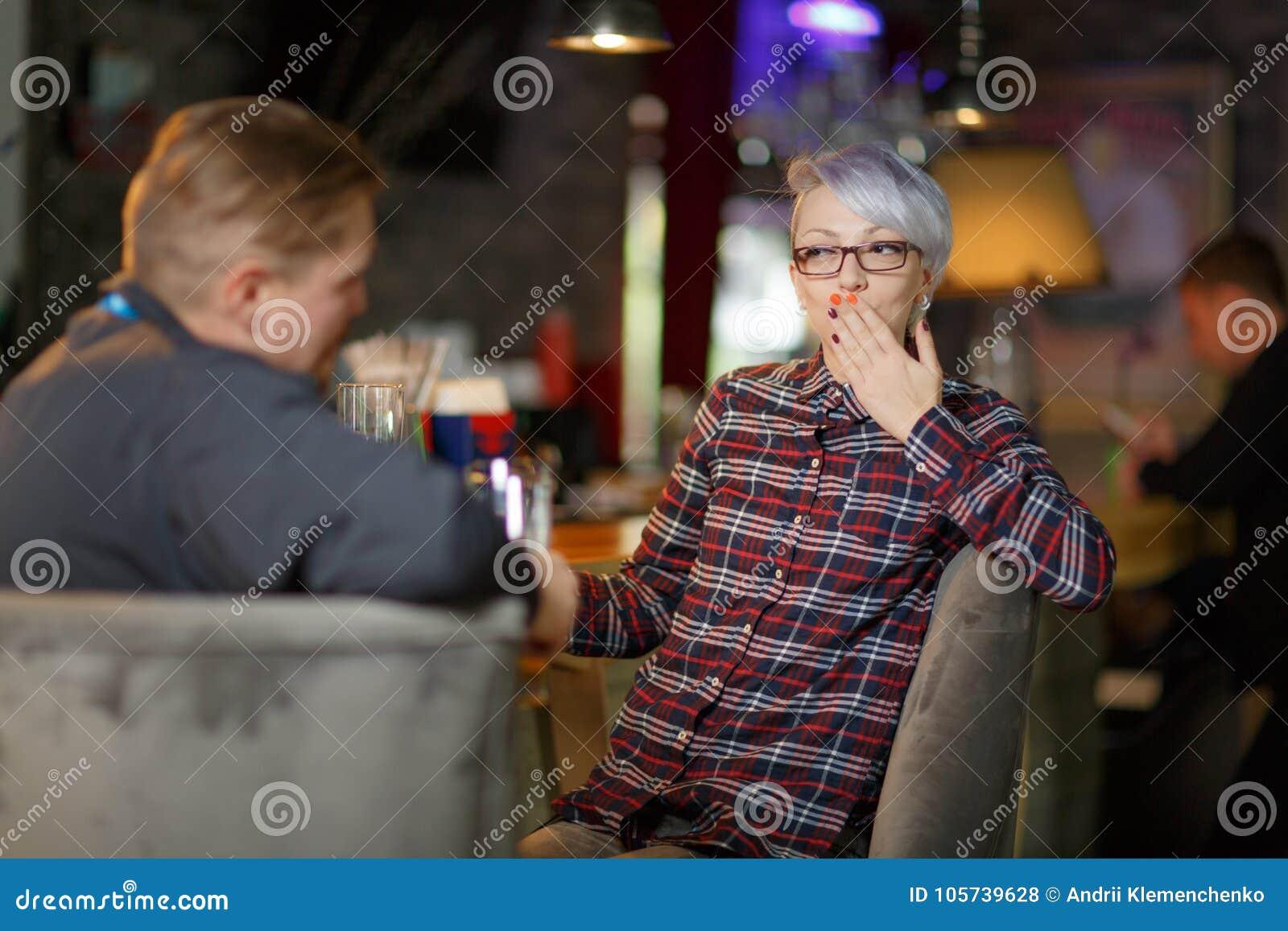 A dans une barre et une bière potable, la fille couvre la bouche de main indoors